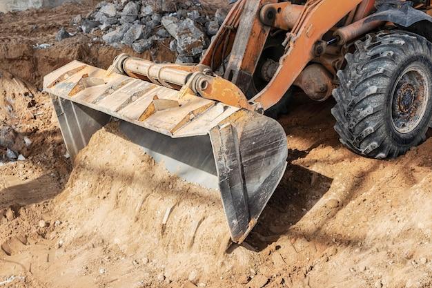 Baggerlader bewegt lehmboden in der ausgrabung zur deponie. baustellenplanung und bodenfräsen mit einem bulldozer.