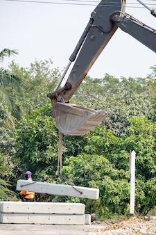 Baggerlader und arbeiter hoben zementblock an