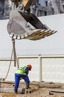 Baggerschaufel heben metallträger mit arbeiterhilfe, baustelle und abgerissenem gebäude