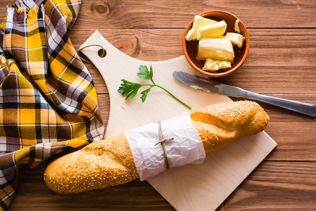 Baguette, butter, messer und petersilie auf einem schneidebrett. ansicht von oben