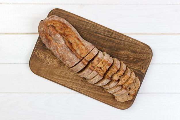 Baguette des französischen brotes geschnitten auf hölzernes brotbrett der weinlese