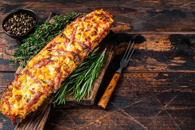 Baguette gefüllt mit schinken, speck, gemüse und käse auf holzbrett