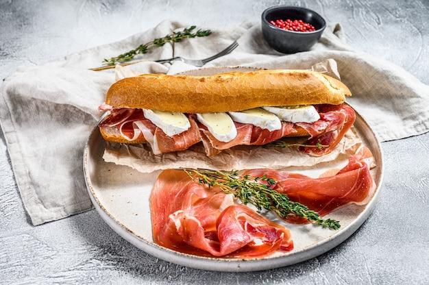 Baguette-sandwich mit jamon ham serrano, paleta iberica, camembert-käse auf dem schneidebrett. , draufsicht.