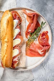 Baguette-sandwich mit jamon ham serrano, paleta iberica, camembert-käse auf dem schneidebrett. grauer hintergrund, draufsicht.