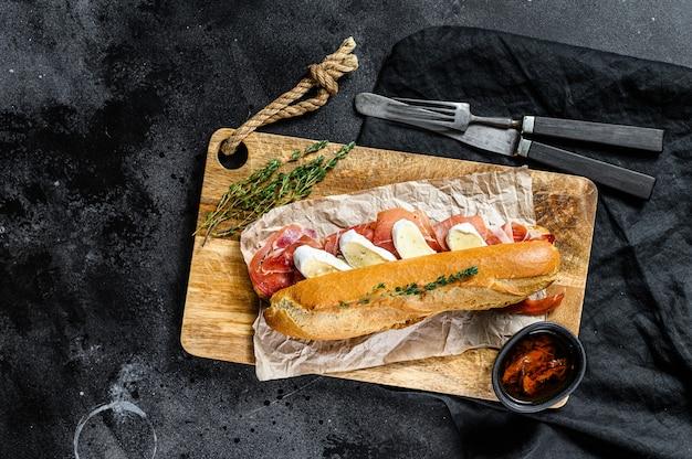 Baguette-sandwich mit jamon ham serrano, paleta iberica, camembert-käse auf dem schneidebrett. schwarzer hintergrund, draufsicht.