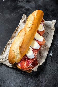 Baguette-sandwich mit jamon ham serrano, paleta iberica, camembert-käse.