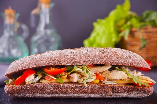 Baguettesandwich mit truthahnbrust, käse, salat, rucola, tomaten und zwiebeln auf einem schwarzen teller.