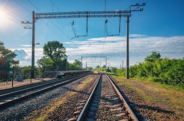 Bahnhof am hellen sonnigen tag im sommer. eisenbahn in europa. schwerindustrie. industrielandschaft mit bahnsteig, grünen bäumen, blauer himmel mit wolken und sonnenlicht. transport