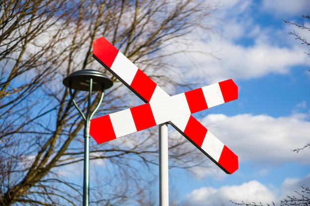 Bahnübergangsschild gegen kahle bäume und bewölkten blauen himmel
