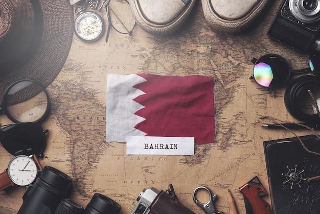 Bahrain-flagge zwischen dem zubehör des reisenden auf alter weinlese-karte. obenliegender schuss