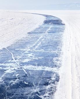 Baikalsee im winter. eisstraße auf dem gefrorenen baikalsee. wintertourismus