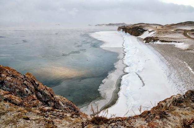 Baikalsee und felsen in der dezemberkälte. zeit des einfrierens. eisschollen schwimmen auf dem wasser