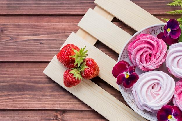 Baiser. das konzept der feier. valentinstag geschenk. selektiver fokus, kopienraum-eibisch, flaumiger nachtischzefir, rosa strudelmeringe und erdbeere.