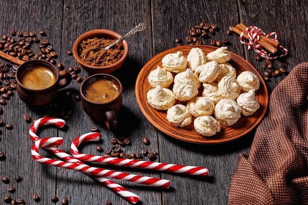 Baiser-kekse serviert auf einem teller mit weihnachtszuckerrohr, kaffeetassen, kaffeebohnen, braunem zucker und zimtstangen auf dunklem holzhintergrund, draufsicht, nahaufnahme