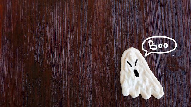 Baisergeister, kinderfutter für helloween, liegen auf einem holztisch
