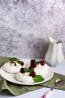 Baiserkuchen, dekoriert mit schlagsahne, kirschen und minzblättern auf einem weißen teller, mit einem milchkrug, seitenansicht mit kopierraum