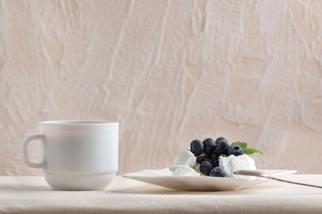 Baiserkuchen mit blaubeeren und einer tasse kaffee dekoriert. leckeres dessert.