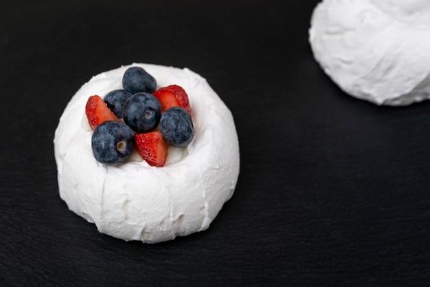 Baiserkuchen mit frischen erdbeeren und blaubeeren. kuchen anna pavlova. nahansicht.