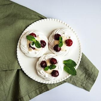 Baiserkuchen mit schlagsahne, kirschen und minzblättern auf einem weißen teller und einer grünen serviette verziert, draufsicht mit kopierraum
