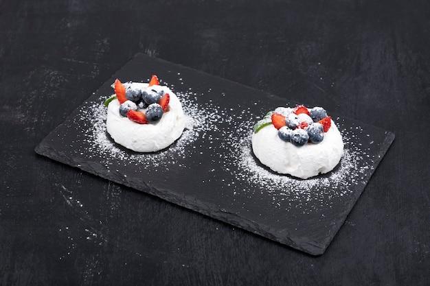 Baiserkuchen und frische beeren auf schwarzem hintergrund. kuchen anna pavlova.