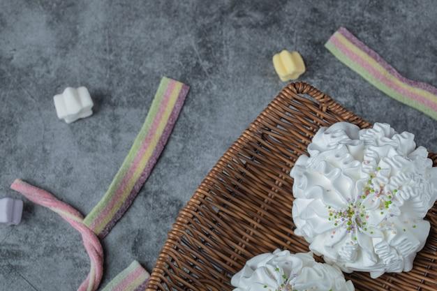 Baiserplätzchen mit gemischtem kokosnusspulver und mini-geleebonbons herum.