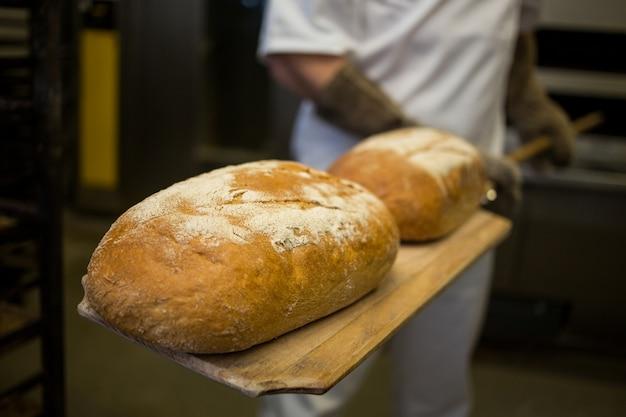 Baker entfernen gebackene brötchen aus dem ofen