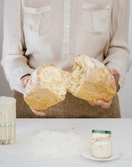 Baker hält ein frisch gebackenes sauerteigbrot in den händen