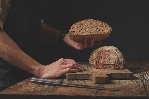 Baker hält halb frisch gebackenes bio-brot auf dunklem hintergrund