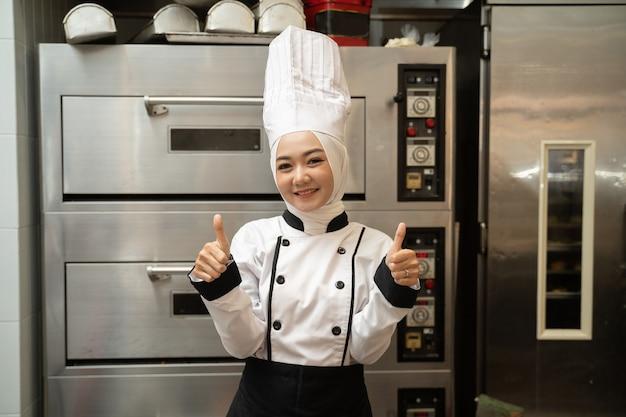 Baker muslim zeigt daumen hoch und lächelt in die kamera, die vor dem großen ofen steht