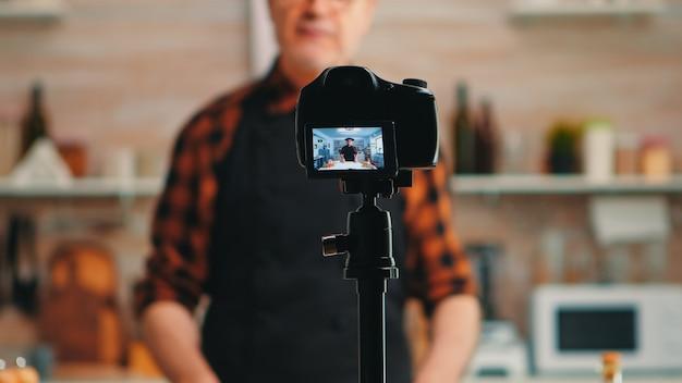 Baker präsentiert die verwendung von weizenmehl während der aufnahme eines video-tutorials. pensionierter blogger-koch-influencer, der internet-technologie verwendet, kommuniziert und blogging in sozialen medien mit digitaler ausrüstung fotografiert