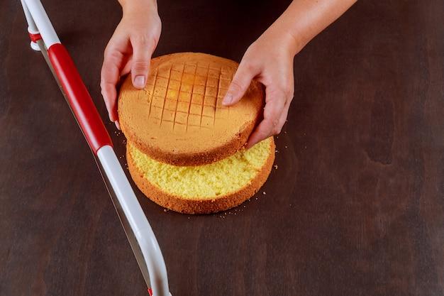 Baker schnitt die oberseite des biskuitkuchens mit einem gezackten richtkuchen ab. eine torte backen.