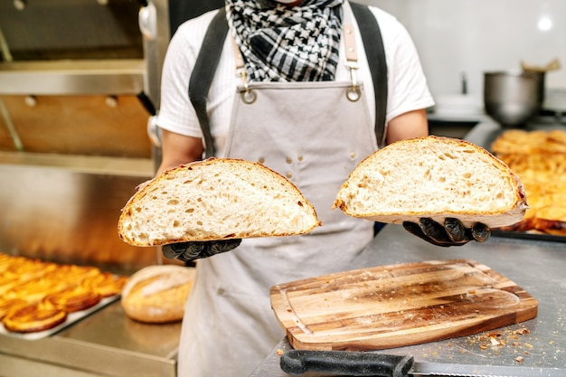 Baker zeigt mit den händen die krume eines laibs weizenbrot und wird von schwarzen handschuhen geschützt