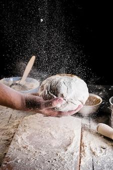 Bakers, die mehl über den knetteig besprühen