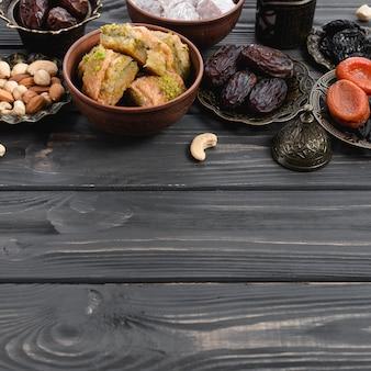 Baklava-süßigkeiten der türkischen freude; trockenfrüchte und nüsse auf schreibtisch aus holz
