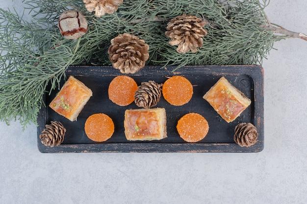 Baklava und marmeladen auf schwarzem teller mit tannenzapfen.