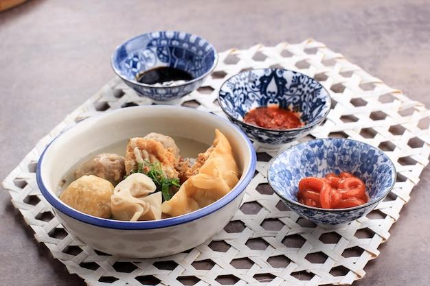 Bakso arema, fleischbällchen food special aus malang east java indonesien. nahaufnahme, auf holzbrett und rustikalem tisch. serviert mit sojasauce, sauce und chilipaste