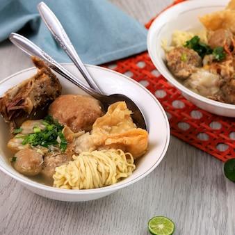 Bakso malang komplit, fleischbällchensuppe mit verschiedenen beilagen wie nudeln, gebratenem shiumay oder rippchen. auf dem tisch serviert (bakso iga)