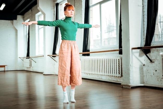 Balance. hübsches rothaariges mädchen mit einem brötchen auf ihrem kopf, das konzentriert sieht, während sie ausgleichsübung machen
