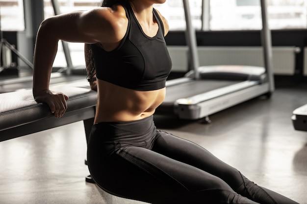 Balance. junge muskulöse kaukasische frau, die im fitnessstudio mit ausrüstung übt. sportliches weibliches modell, das geschwindigkeitsübungen macht, ihre hände, brust, oberkörper trainiert. wellness, gesunder lebensstil, bodybuilding.