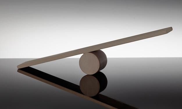 Balance-konzept, brett auf holzhut wie balance auf schwarzem hintergrund isoliert,
