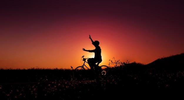 Balance, lebensfreude und harmoniekonzept. silhouette der glücksperson auf dem fahrrad mit erhobenen armen zum ausgleich des körpers bei sonnenaufgang oder sonnenuntergang im öffentlichen naturpark