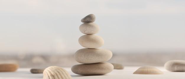 Balancierende steine übereinander mit schönem verschwommenem himmelshintergrund