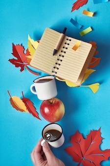 Balancierender turm aus kaffeetassen, herbstlaub und leerem notizbuch