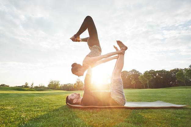Balancierendes yoga stellt gesunde und junge paare dar, die zusammen im morgenpark acro-yoga praktizieren