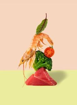 Balansing garnelen, thunfisch, brokkoli und kirschtomaten auf einem hellgrünen und rosa hintergrund. moderne trendige food-stillleben-fotografie. konzept pescataian dien.
