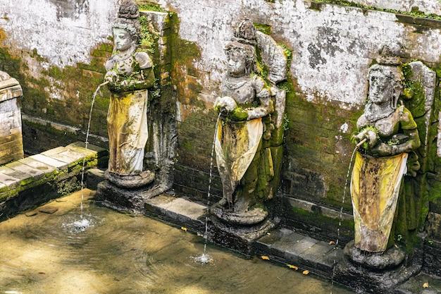 Balinesische architektur. alter brunnen, der mit kreativen skulpturen von göttinnen im exotischen land geschmückt wird