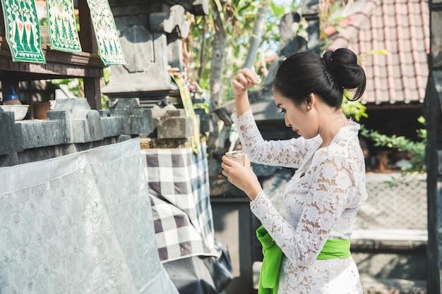 Balinesische frau, die rituell canang sari anbietet und betet