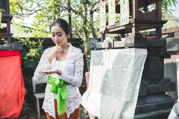 Balinesische frau, die rituellen betenden tempel tut