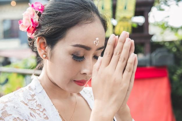 Balinesische frau, die tempel auf kleinen schreinen in häusern betet