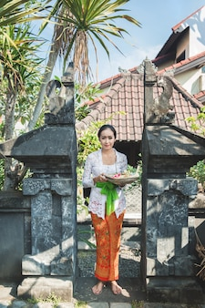Balinesische frau, die traditionelle kleidung trägt, die canang sari bringt